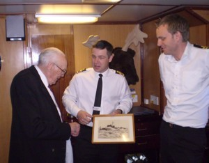 Jack Roberts presents the CO of the current HMS Cattistock with a picture of her predecessor